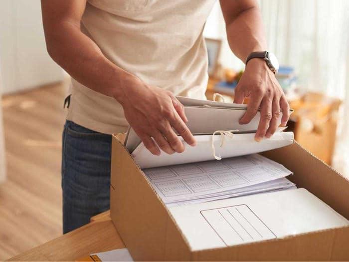 persona che sistema documenti da uno scatolone