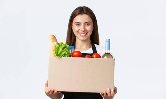 Donna che sorride con cesto di frutta in mano - raccontiamo la nostra integrazione Glovo - Cassa in Cloud
